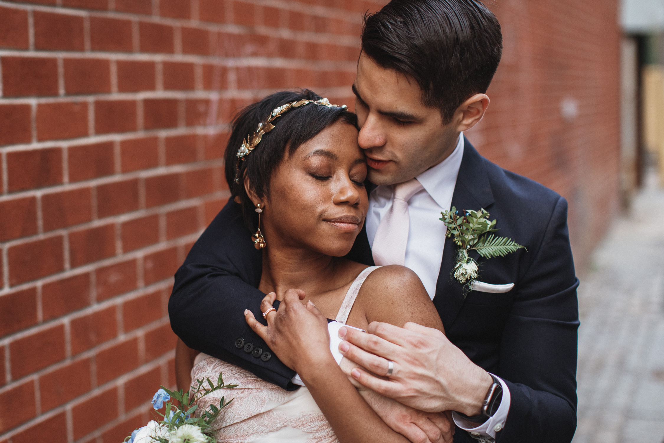 Man hugs woman from behind for their wedding photos in DUMBO Brooklyn