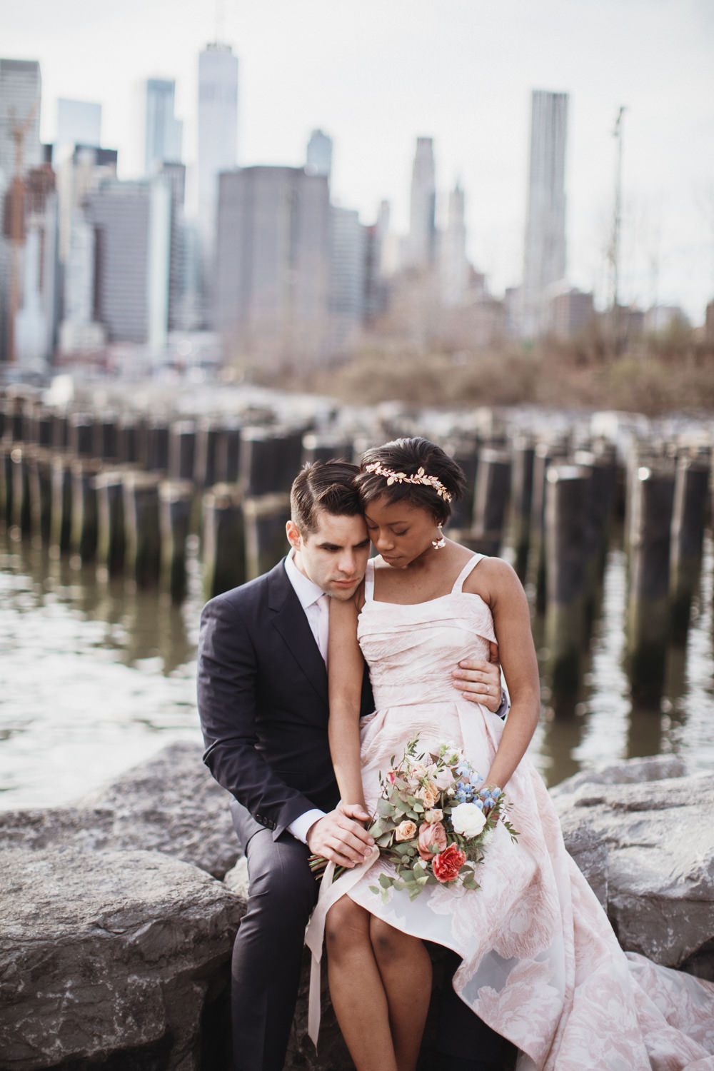 Wedding Photos in DUMBO Brookyn - Woman sits close to man on rocks holding a bouquet