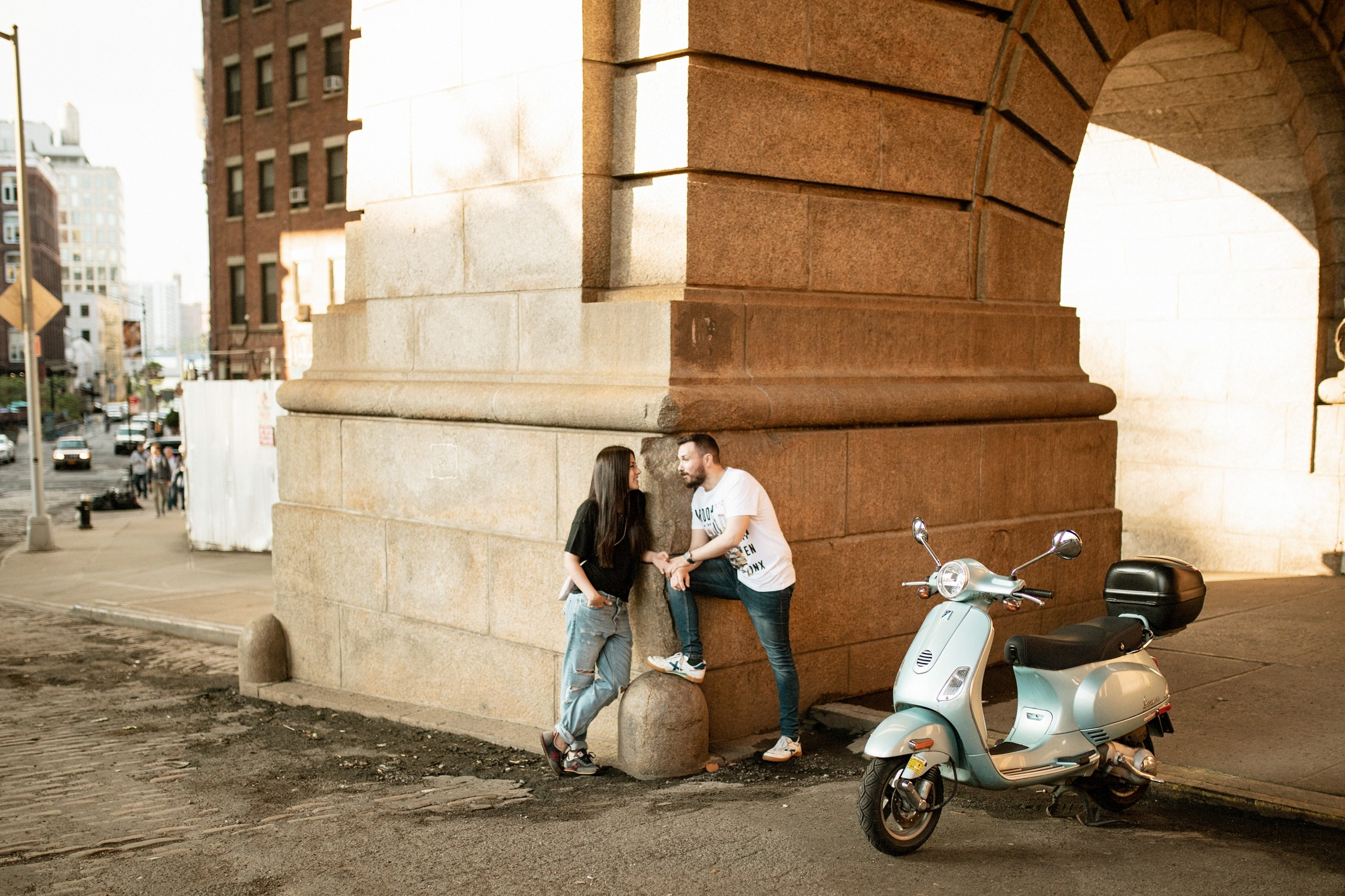 Engagement Photos in DUMBO - Couple poses by a parked Vespa under the Brooklyn Bridge