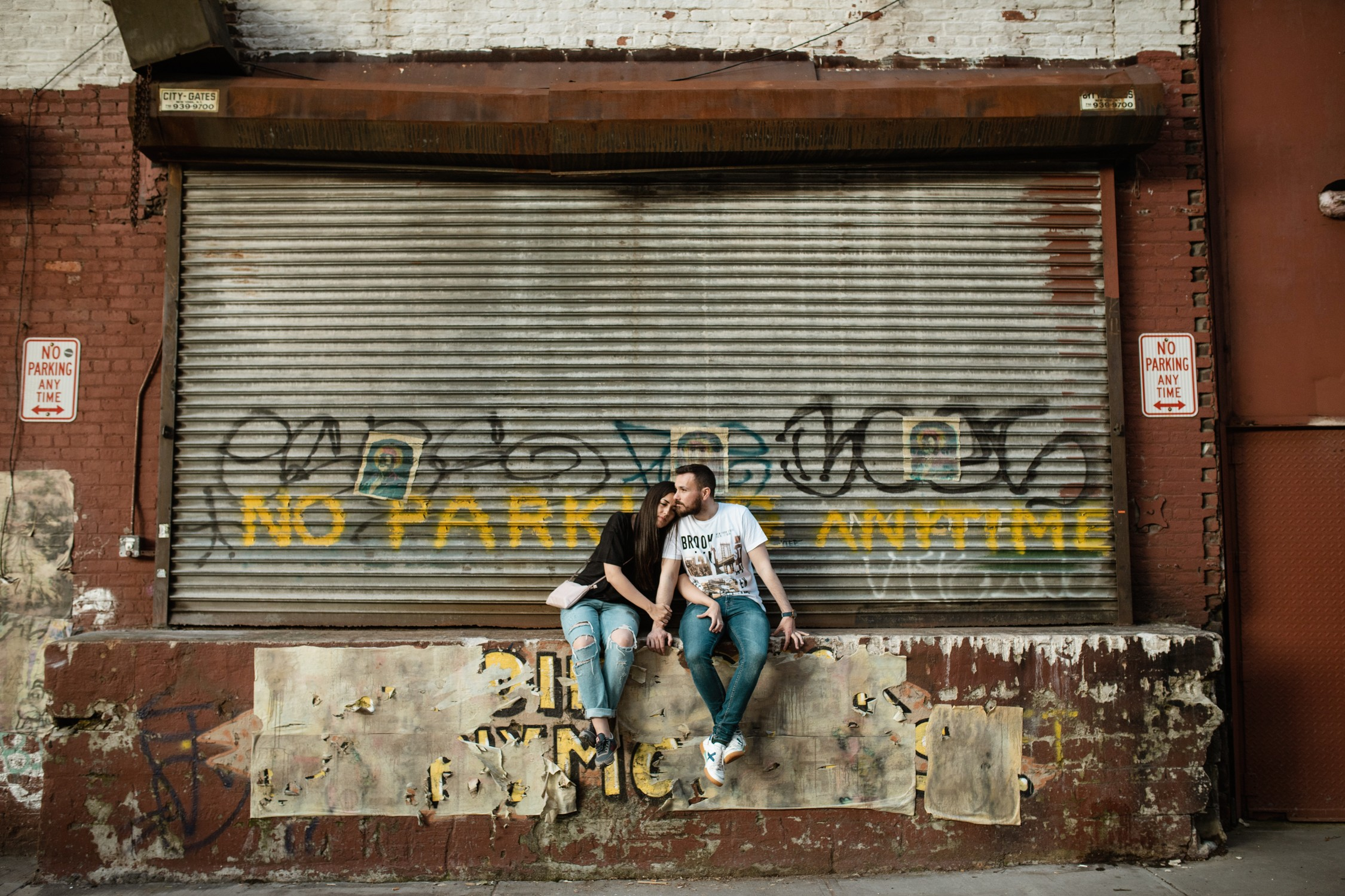 Engagement Photos in DUMBO - Couple sitting next to each other by a metal door