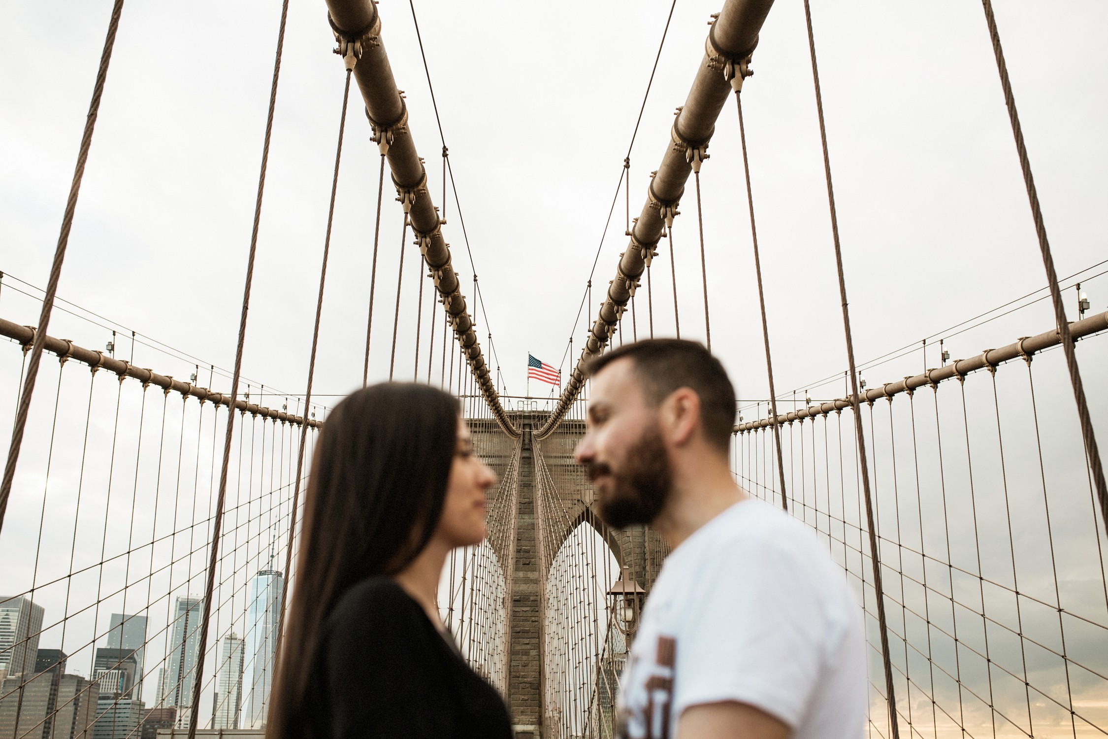 Engagement Photos in DUMBO - Couple facing each other the Brooklyn Bridge