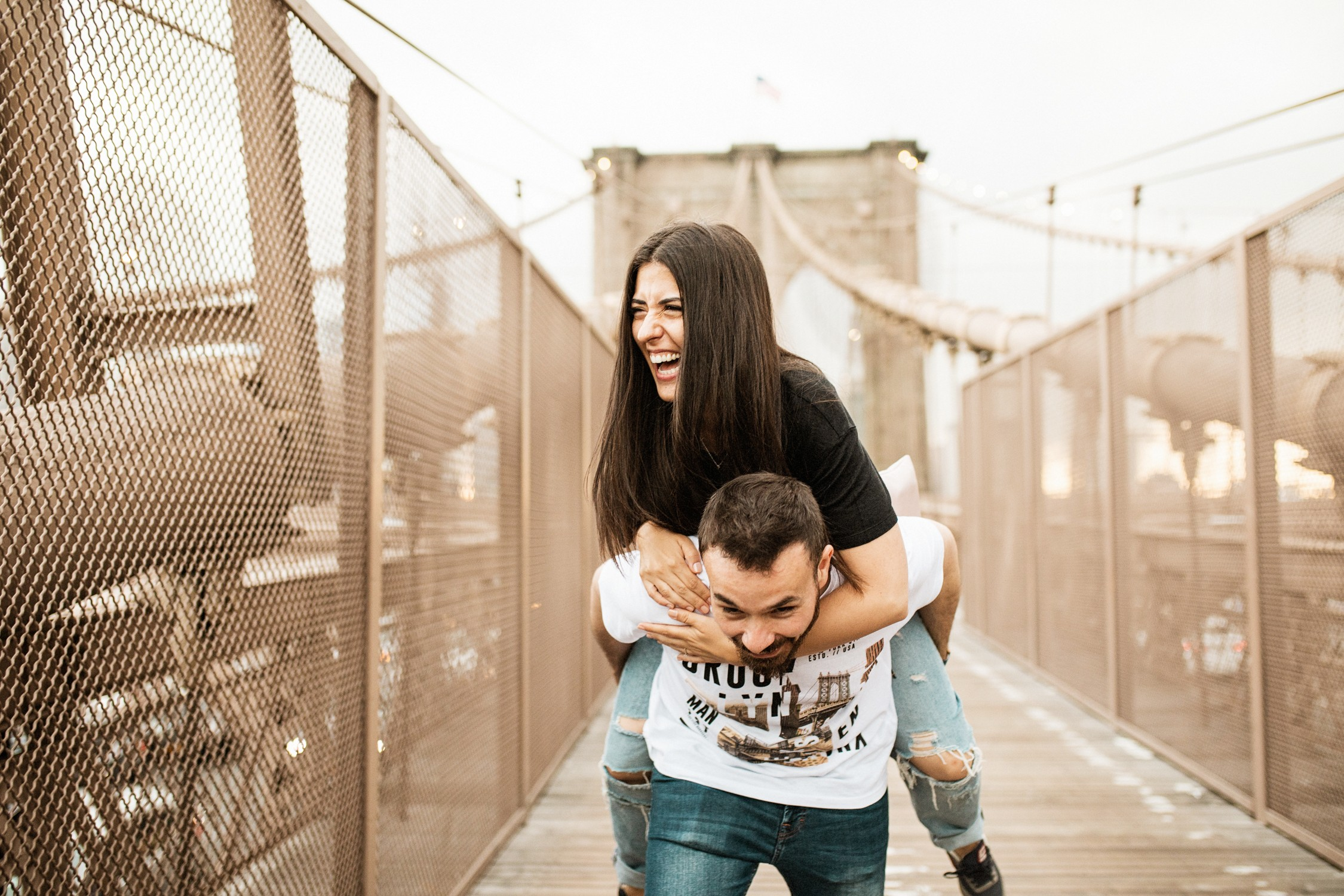 Engagement Photos in DUMBO - Couple laughing and piggyback rides on the Brooklyn Bridge