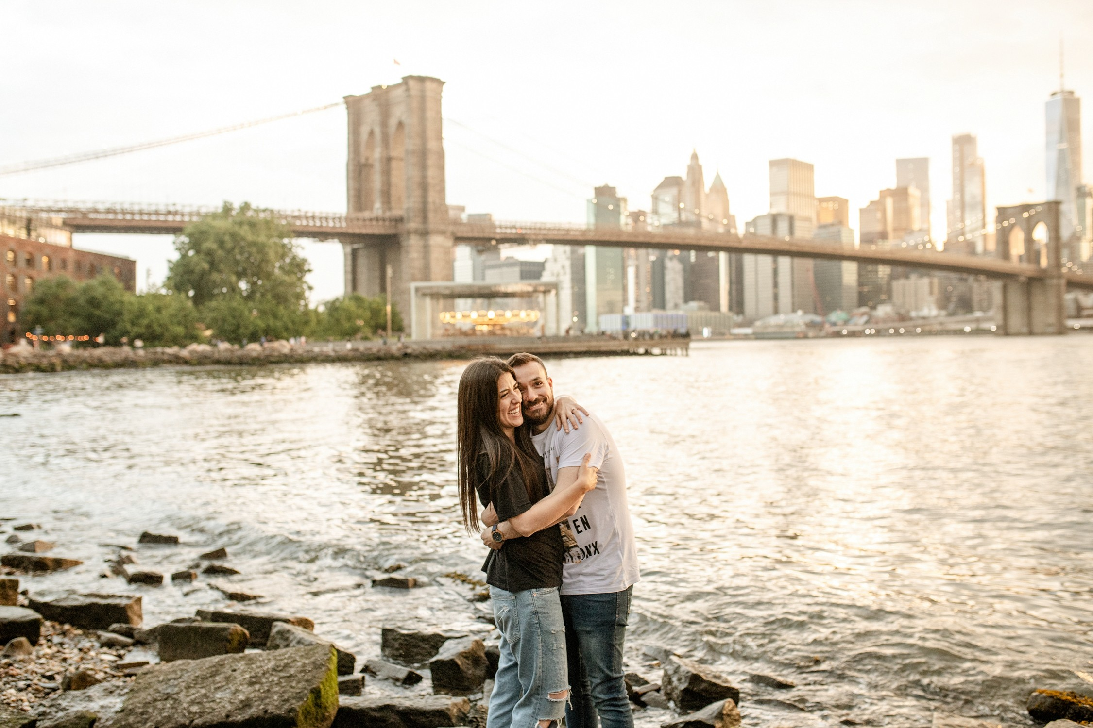 Engagement Photos in DUMBO - Couple holding each other on Pebble Beach at sunset with the Brooklyn Bridge in the background