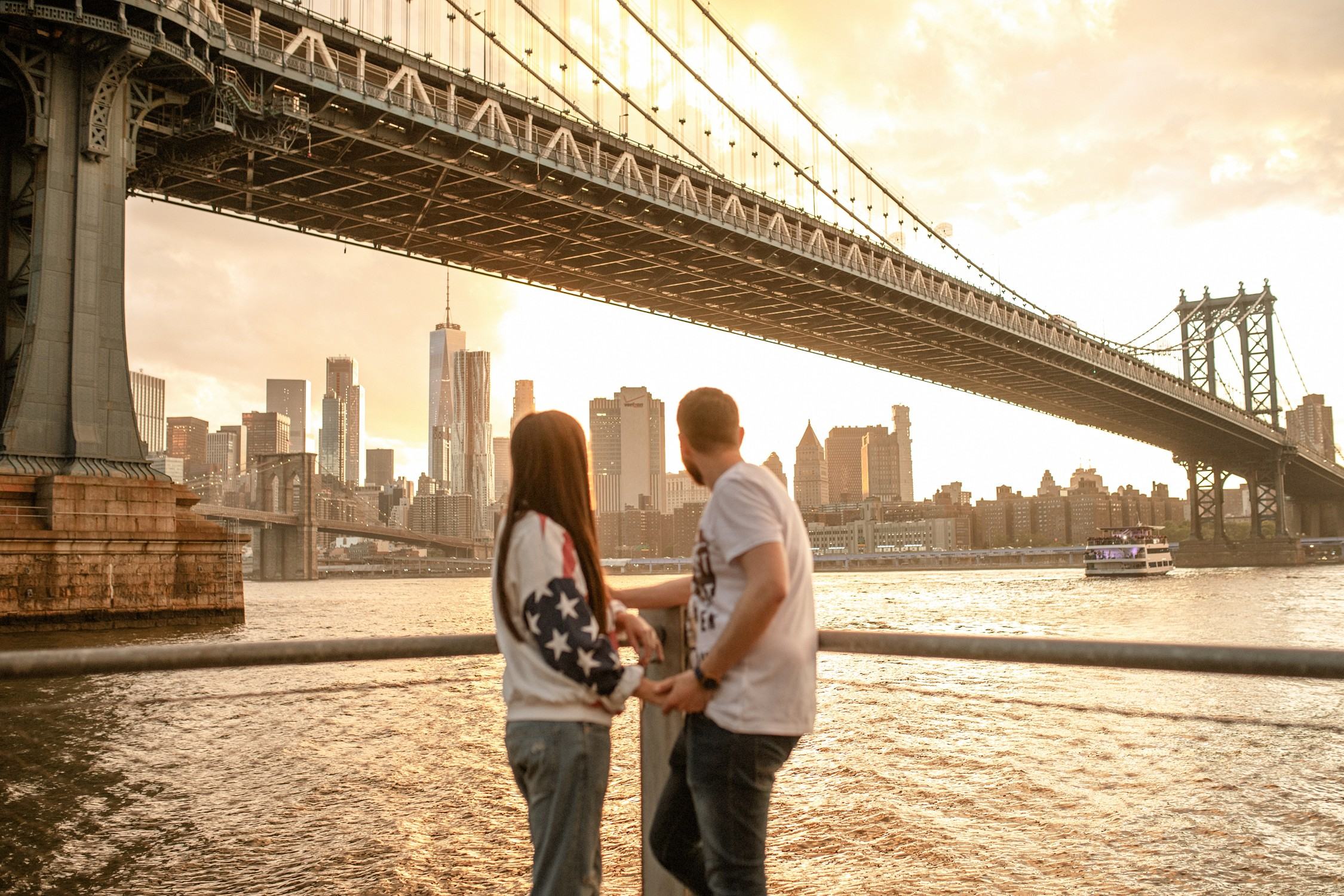 Engagement Photos in DUMBO - A couple looks at the sunset on the NYC skyline