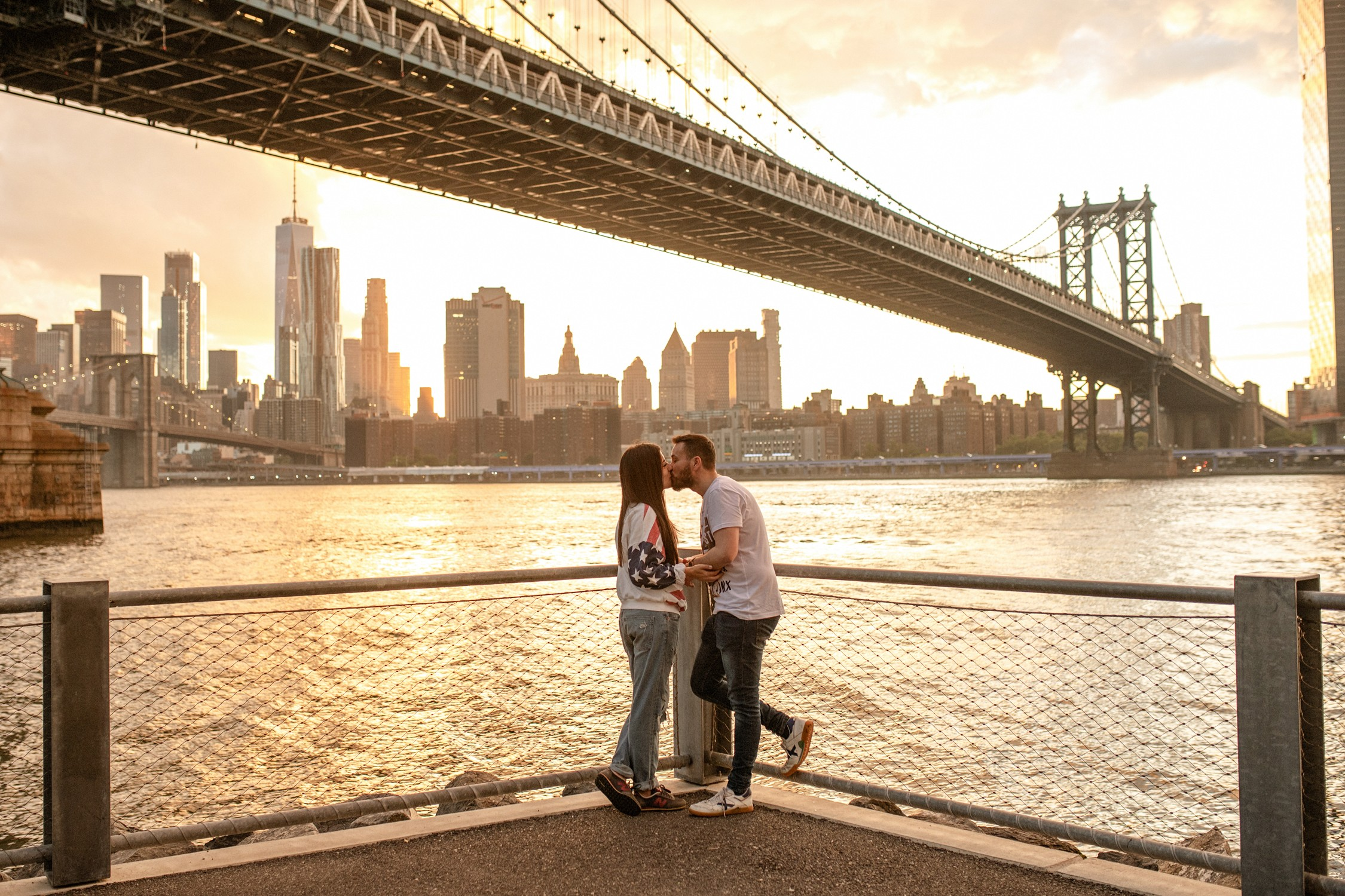 Engagement Photos in DUMBO - A couple looks at the sunset and kissing