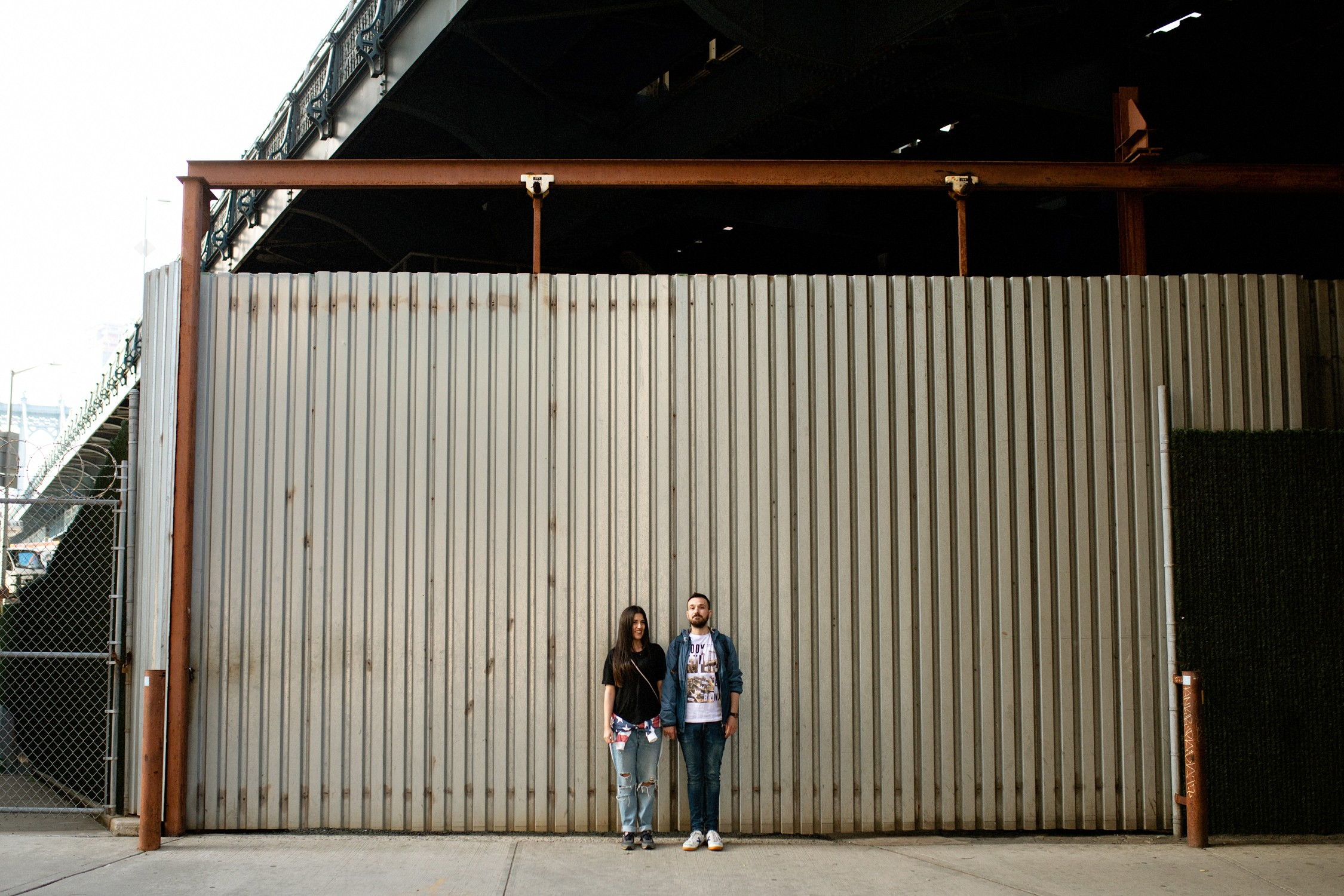 Engagement Photos in DUMBO - Couple standing side by side and looking at the camera