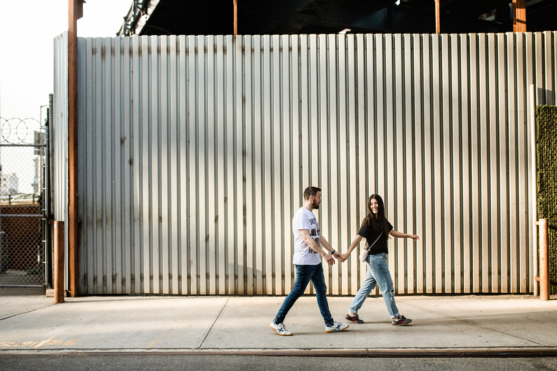 Engagement Photos in DUMBO - Couple walking in the streets below the Brooklyn Bridge