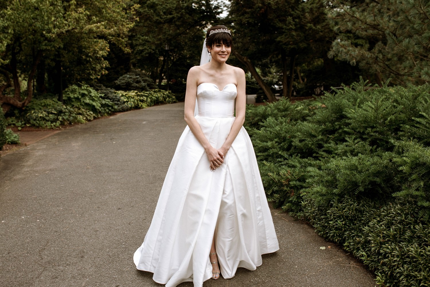 Bride stands in a long white wedding dress before the first look at the Brooklyn Botanic Garden