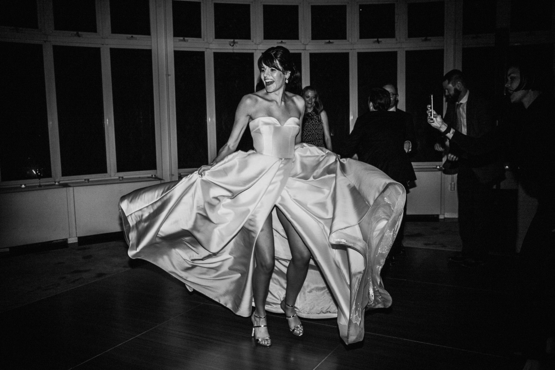 Bride dances with a luxurious wedding dress by Reem Acra at the Brooklyn Botanic Garden