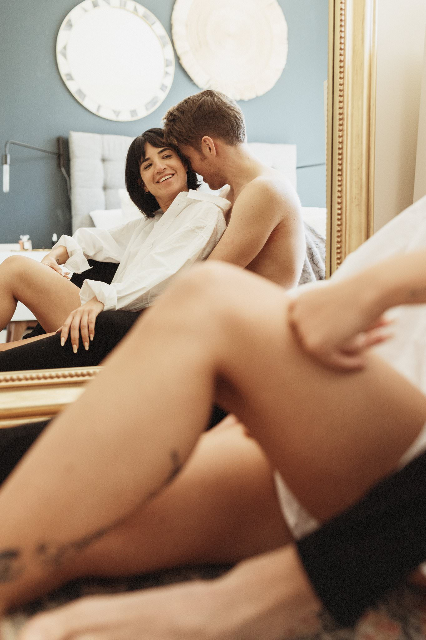 Woman in white shirt and man sit and hold each other in front of a mirror in a couples boudoir session